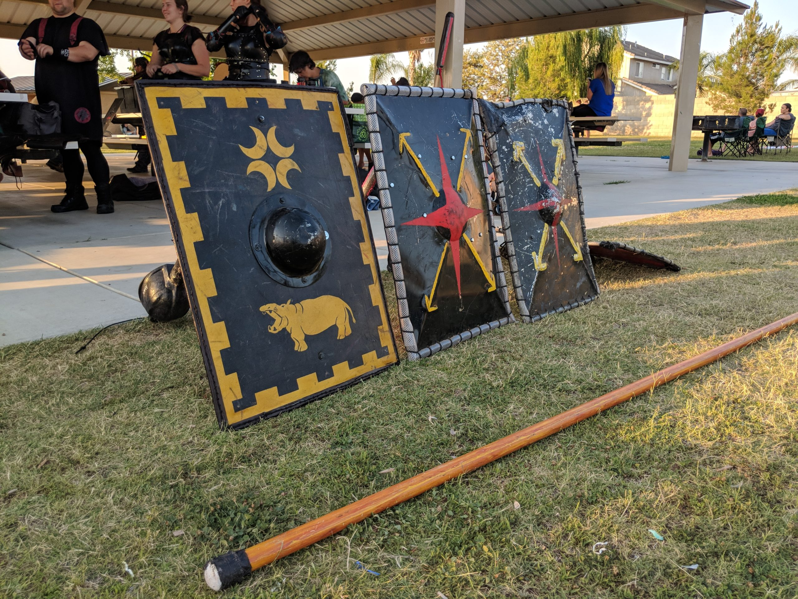 Three shields stand propped up behind a rattan polearm near the pavilion where we hold fighter practice